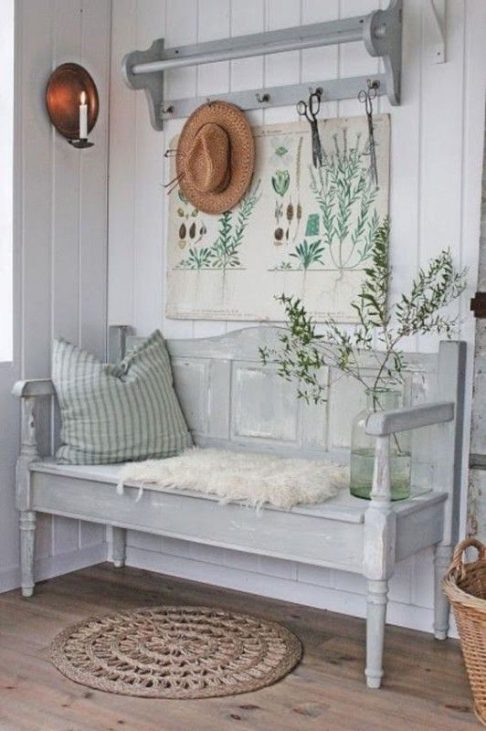 a rustic vintage entryway with a whitewashed bench and a shelf, with botanical posters, candles, a basket and a hat is a lovely space