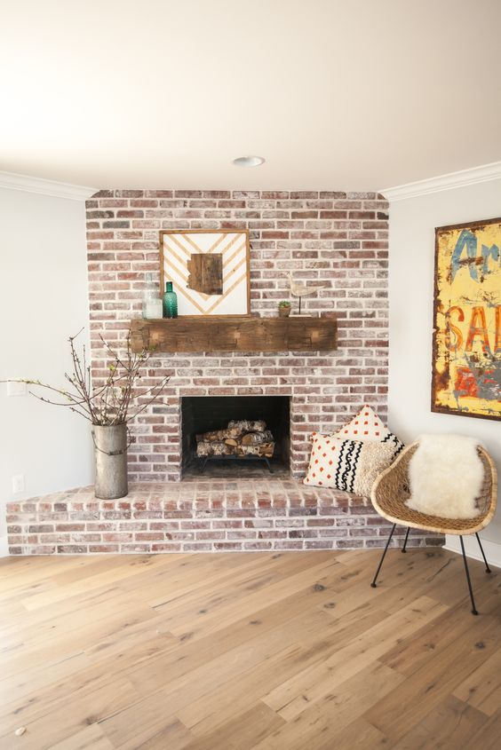 a rustic whitewashed red brick fireplace with a wooden mantel, mid-century modern decor and printed pillows
