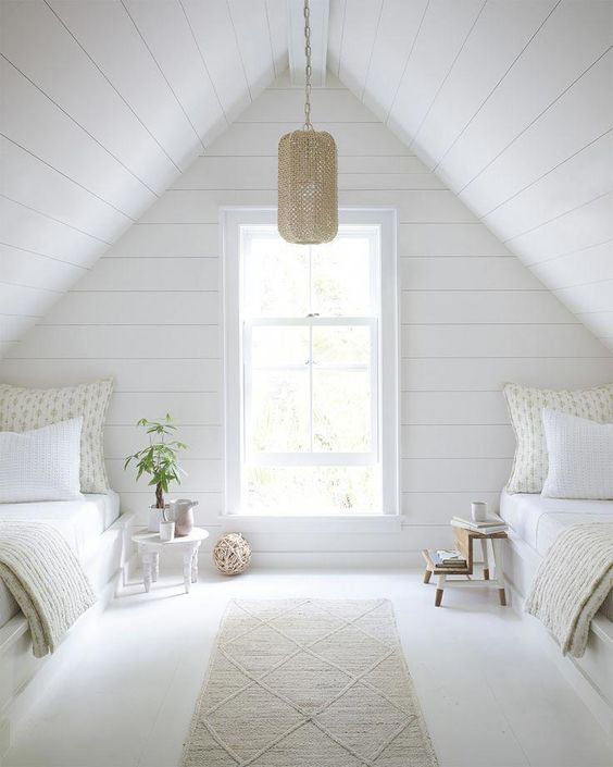 a serene attic guest bedroom with whitewashed wooden walls and white beds, a pendant lamp and neutral printed bedding