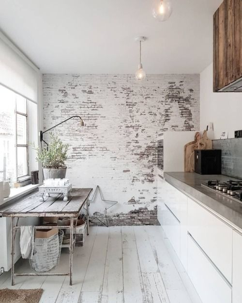 a shabby chic Nordic kitchen with a whitewashed brick wall, sleek white cabinetry, a vintage table and potted plants
