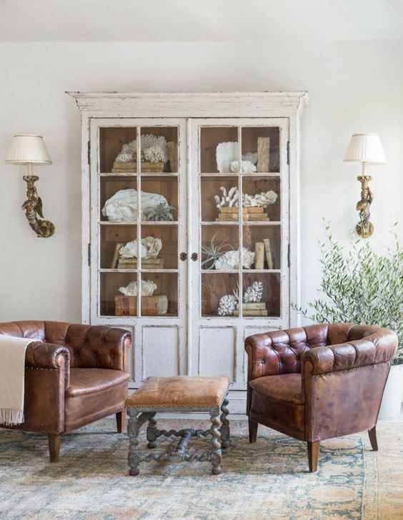 a shabby chic space with a whitewashed display cabinet with glass doors and leather chairs, a leather sotol and wall sconces