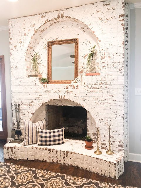 a shabby chic whitewashed fireplace with a mirror, potted greenery, printed pillows and candles in candlesticks