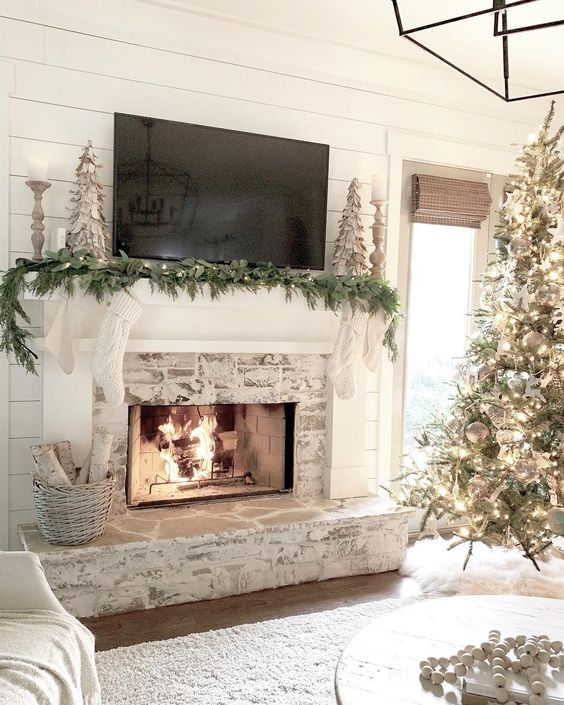 a shabby whitewashed fireplace with a mantel decorated for Christmas and a basket with firewood