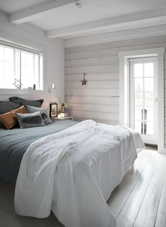 a simple Nordic bedroom with whitewashed wooden walls, a bed with grey and copper bedding, stars and sconces is welcoming