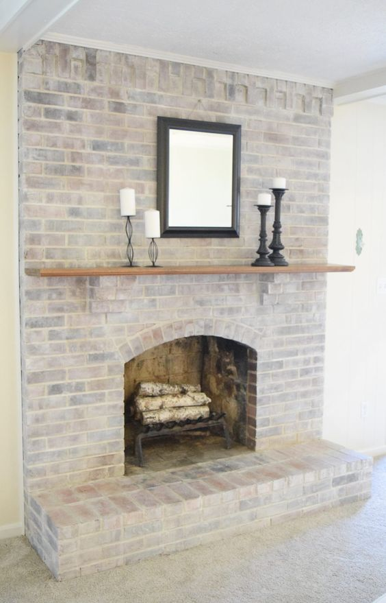 a simple and stylish whitewashed brick fireplace with firewood, a mantel, candles and a mirror for adding coziness to your space