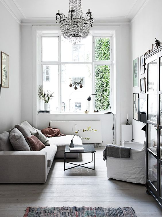 a small Scandinavian living room in a neutral color palette, with comfy and simple furniture, a crystal chandelier and a gallery wall