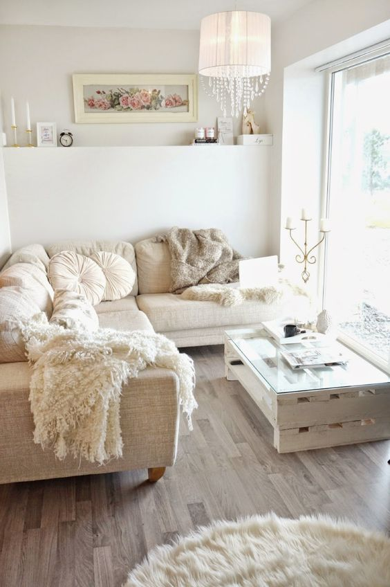 a small and neutral glam living room with a sectional sofa, a pallet table, a fur rug, a lamp with crystals