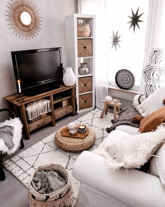 a small boho living room in neutrals, with a white sofa, woven items, a wooden TV unit, stars and a sunburst mirror on the wall
