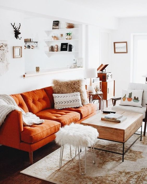 a small boho living room with a rust-colored sofa, printed pillows, a wooden table, mid-century modern furniture and a boho rug