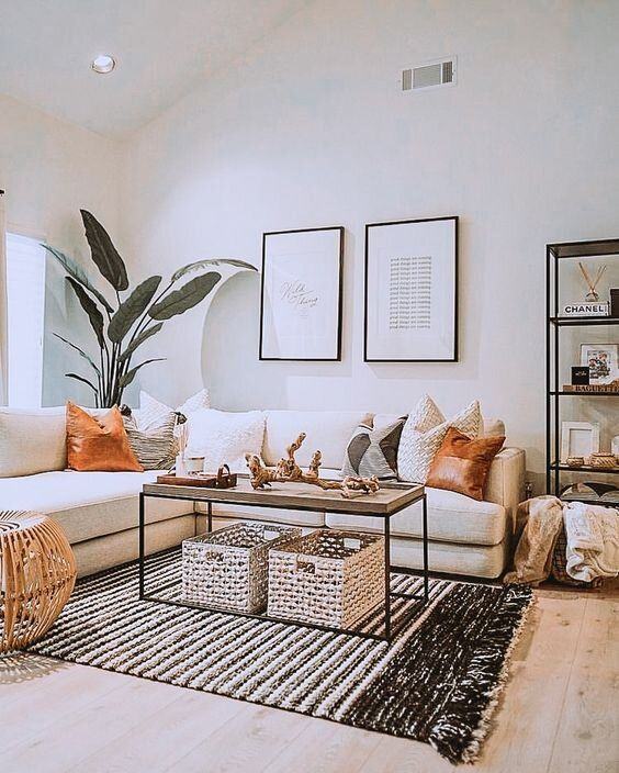 a small boho living room with a white sectional, woven and wooden items, a gallery wall, potted plants and printed pillows