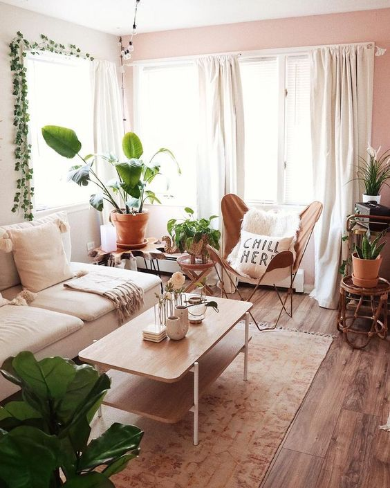 a small boho living room with a white sofa, a leather butterfly chair, a wooden table and lots of plants on stands