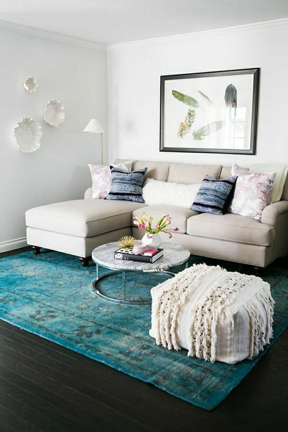 a small colorful living room with a neutral sofa, a turquoise rug, a boho ottoan, pretty plates and an artwork