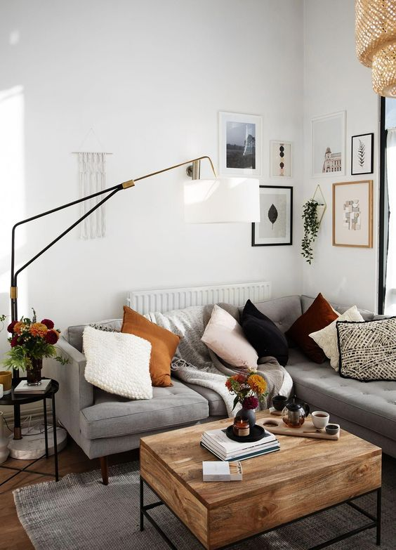 a small contemporary meets boho living room with a grey sectional, a wooden table, a gallery wall, a floor lamp and bright pillows