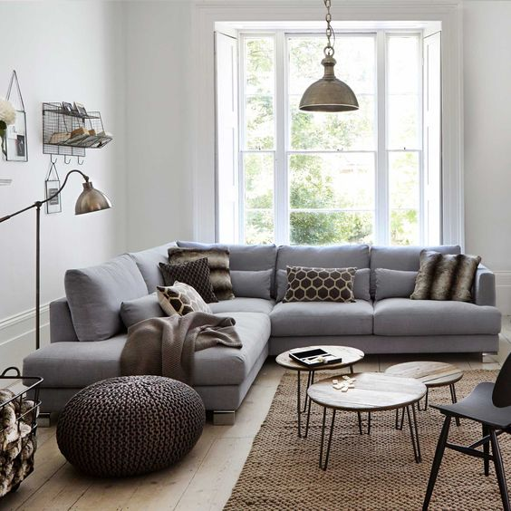 a small cozy living room with a grey sofa, knit ottomans, metal lamps, pin leg tables and a large window