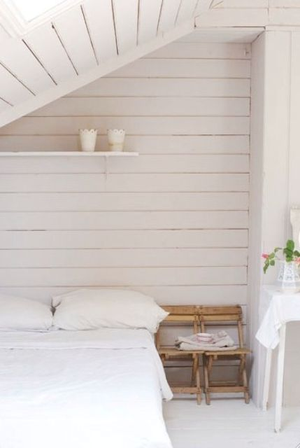 a small neutral bedroom with whitewashed walls and a ceiling, a simple bed and chairs and all neutral linens
