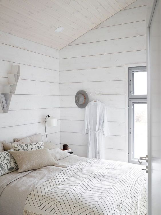 a small neutral bedroom with whitewashed wooden walls, a bed, some sconces and built-in lights is filled with light