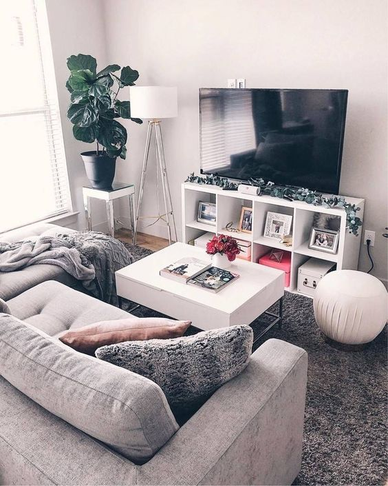 a small yet cozy living room with a small grey sofa, a TV unit, a white table and some lamps plus a potted plant