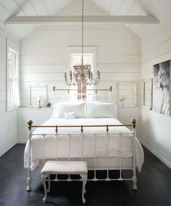 a small yet refined bedroom with whitewashed wooden walls and a ceiling, a metal bed, a sophisticated chandelier and a stool
