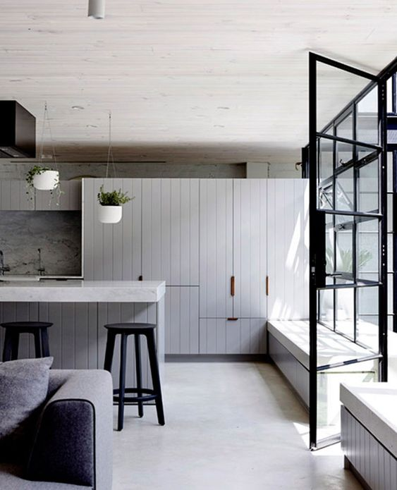 a stylish modern kitchen with a whitewashed concrete floor, grey cabinets, grey furniture and potted greenery