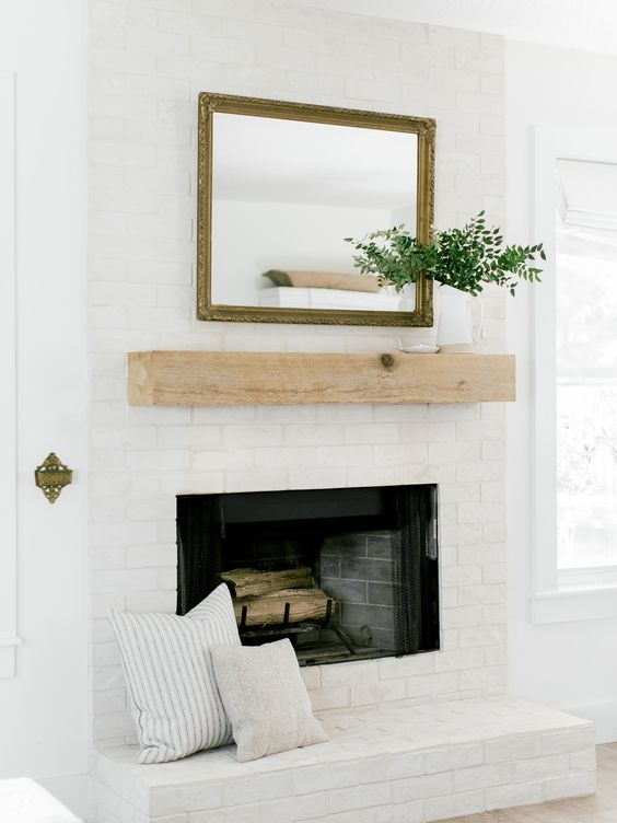 a stylish whitewashed brick fireplace with a wooden mantel, a mirror and greenery plus printed pillows for a cozy feel