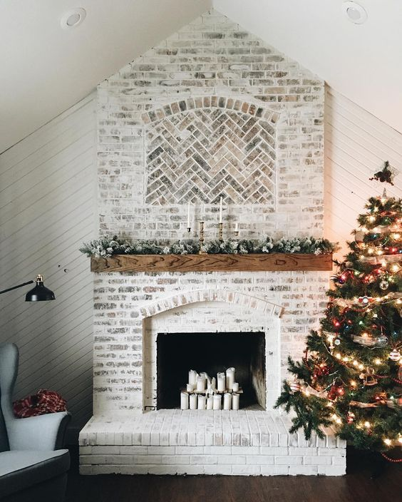 a stylish whitewashed brick fireplace with a wooden mantel with greenery and candles looks very stylish and rustic