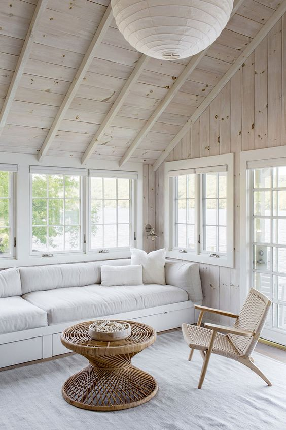 a sunroom with whitewashed wooden walls, a neutral sofa, a woven chair and a rattan coffee table, a pendant paper lamp
