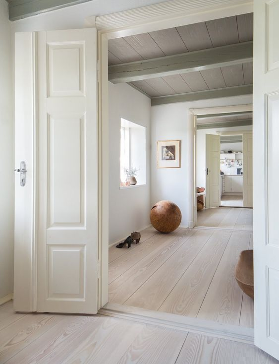 a unique space with white walls, a whitewashed floor, statement furniture and artworks plus lots of light