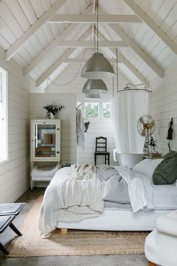 a vintage farmhouse bedroom with a bathroom with whitewashed wooden walls, vintage furniture and lamps and cozy bedding