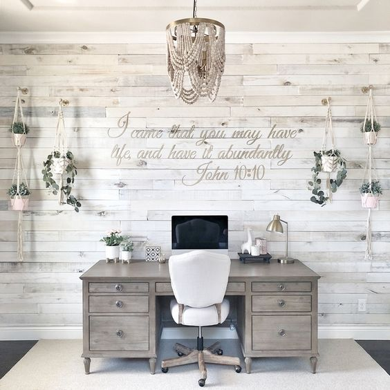 a vintage farmhouse home office with a whitewashed wooden wall, rustic furniture, a beaded chandelier and potted greenery