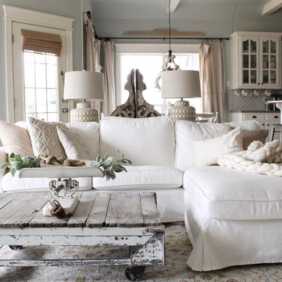 a vintage farmhouse living room with a white sectional, a whitewashed and distressed pallet coffee table, cool lamps and some greenery