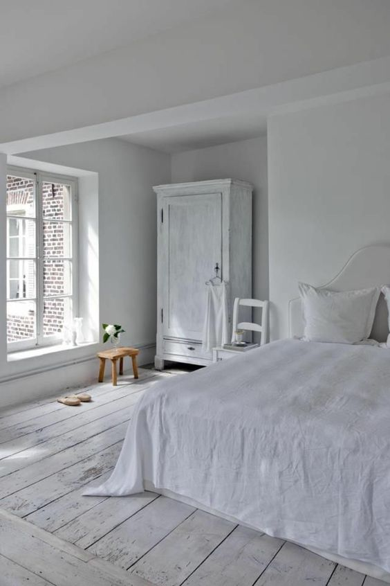 a vintage-inspired bedroom with white walls, a whitewashed floor and whitewashed furniture plus lots of natural light