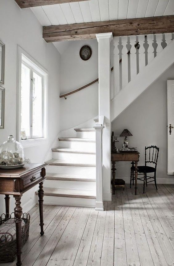 a vintage-inspired entryway in white, with a whitewashed floor, wooden beams and vintage furniture