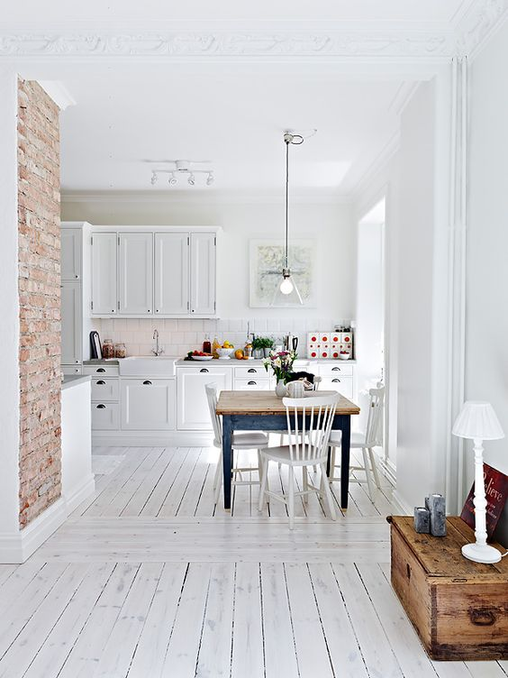 a vintage-inspired kitchen with white walls, a whitewashed floor, white cabinets and a blue dining table