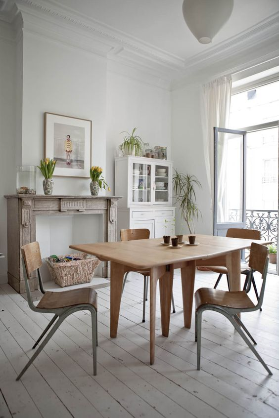 a vintage-inspired living room with white walls and a whiteashed floor, a wooden dining set and a non-working fireplace