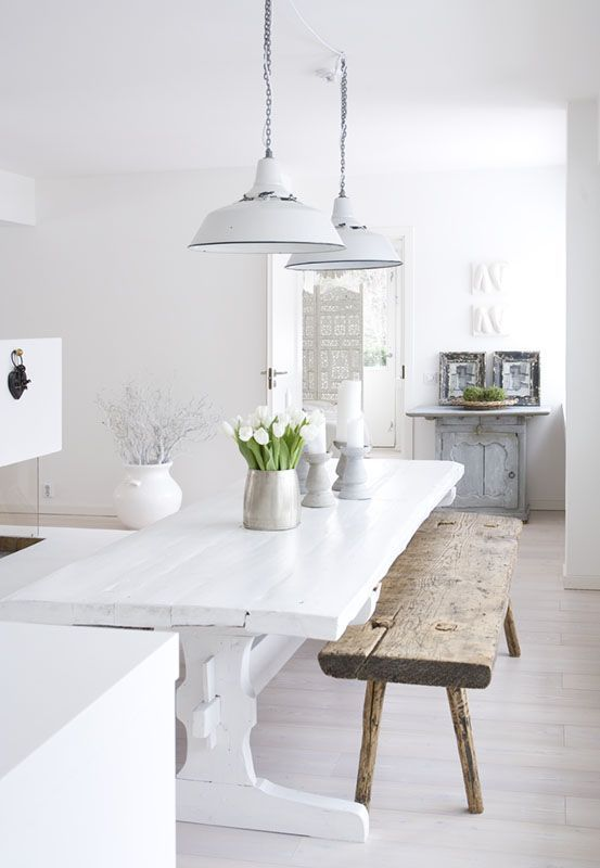 a vintage-inspired white kitchen with white walls and a whitewashed floor, white and stained furniture plus greenery