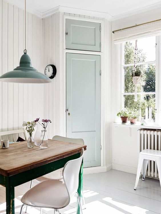 a vintage light-filled space with white walls, a whitewashed floor, lots of natural light and mint touches