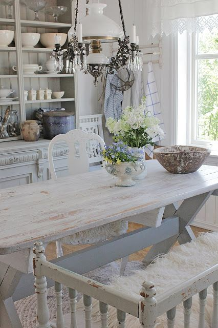 a vintage shabby dining space with a whitewashed table and chairs and a bench, a whitewashed buffet and some touches of blue
