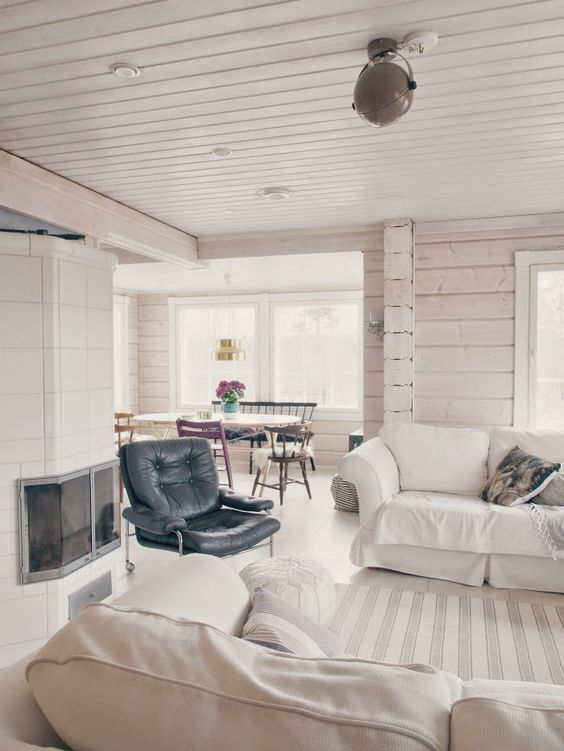a walcoming open neutral layout with whitewashed walls, chic furniture, a hearth and some printed bedding