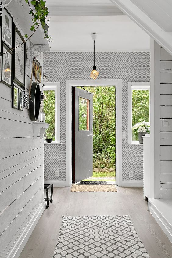 a welcoming Nordic entryway with wallpaper walls, a whitewashed floor and potted blooms plus a pendant lamp