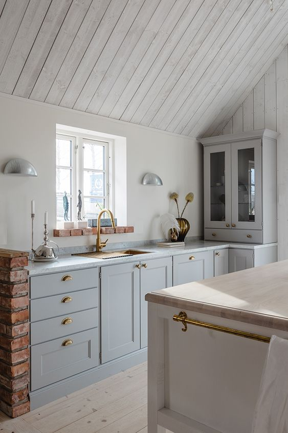 a welcoming neutral kitchen with whitewashed wooden walls and a ceiling, grey cabinets, a white kitchen island and touches of gold