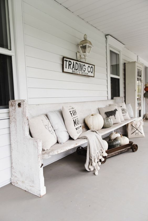a white farmhouse porch with a whitewashed bench, neutral and printed pillows, a cart with pumpkins, a blanket and a sign