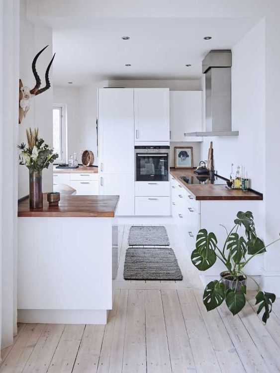 a white kitchen with a whitewashed floor, white cabinets with butcherblock countertops and potted greenery