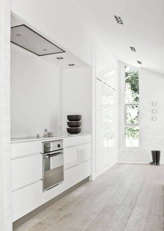 a white minimalist kitchen with a whitewashed floor, sleek cabinets and lots of natural light flooding the space