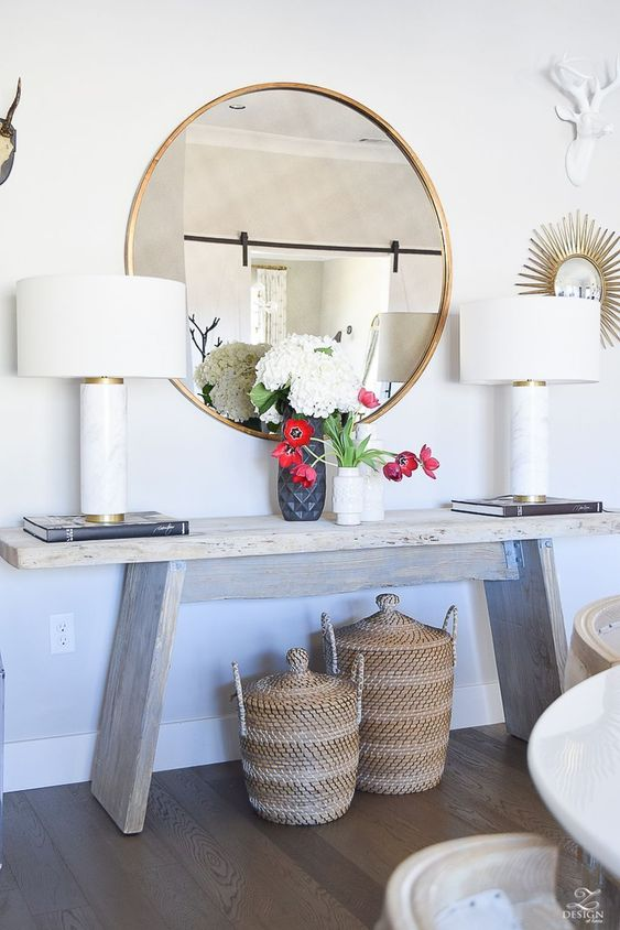 a whitewashed bench is a beautiful alternative to a console, baskets with lids for storage, cool lamps and a round mirror add interest