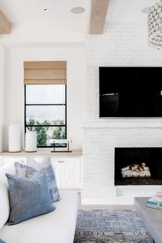 a whitewashed brick fireplace brings coziness to the neutral coastal living room and makes it cozier