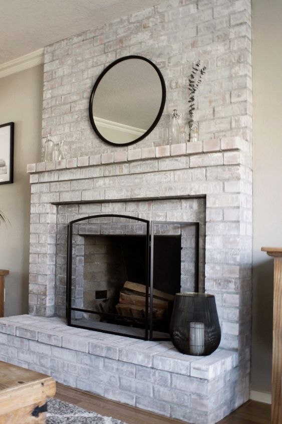 a whitewashed brick fireplace with a brick mantel, a round mirror, a metal frame and a candle lantern is stylish
