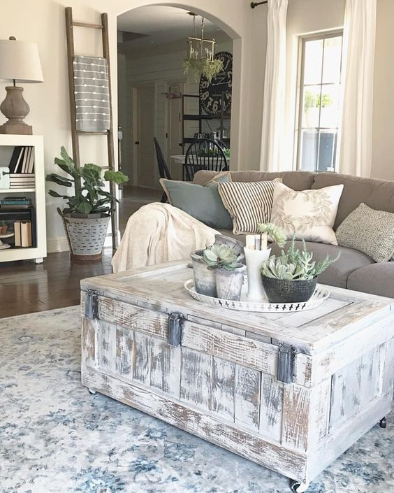 a whitewashed chest as a coffee table on casters and a tray with potted plants for finishing off a farmhouse living room