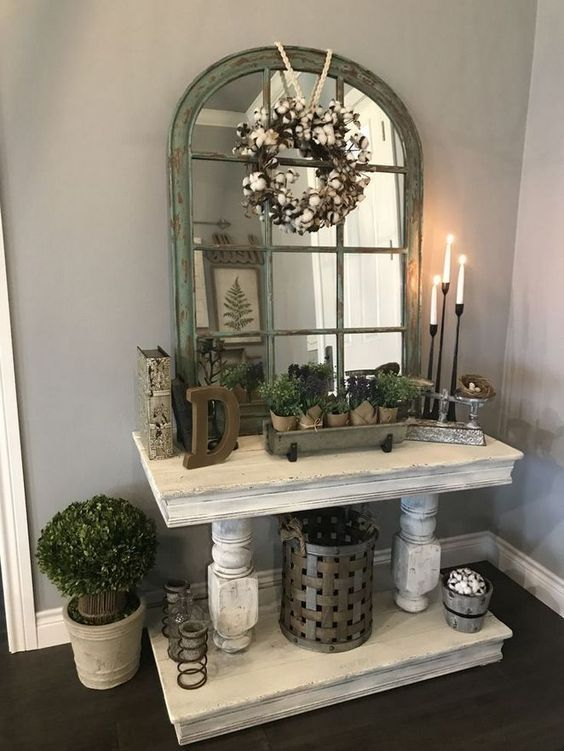 a whitewashed console table, potted plants, a cotton wreath, candles and candleholders for a refined vintage entryway