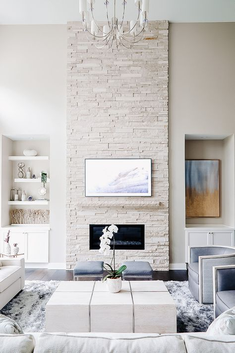 a whitewashed faux stone fireplace with a small mantel and an artwork adds warmth and coziness to the neutral room