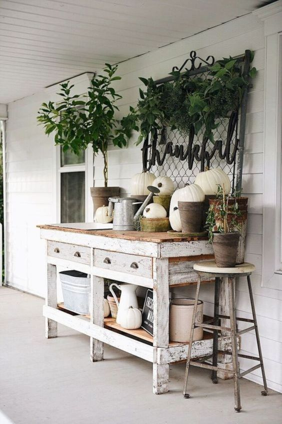 a whitewashed gardening table with lots of pumpkins, greenery, watering cans and jugs is a cool idea for a rustic porch